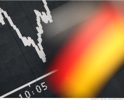 A German flag of a trader supporting the German national football team hangs in front of a board displaying Germany's share index DAX on June 18, 2012 at the stock exchange in Frankfurt/M., western Germany. German stocks opened 1.21 percent higher as investors cheered a weekend election victory for Greece's main pro-bailout party, easing fears Athens may drop out of the eurozone. AFP PHOTO / DANIEL ROLAND        (Photo credit should read DANIEL ROLAND/AFP/GettyImages)